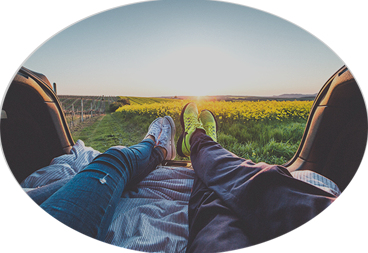 Oval photo of two pairs of feet stretched out watching the sunset